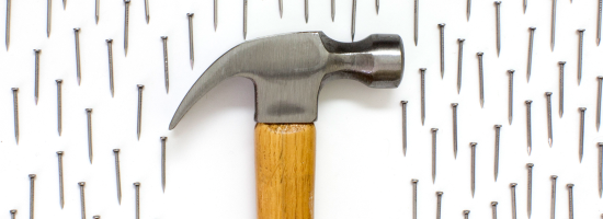 A big hammer surrounded by small nails